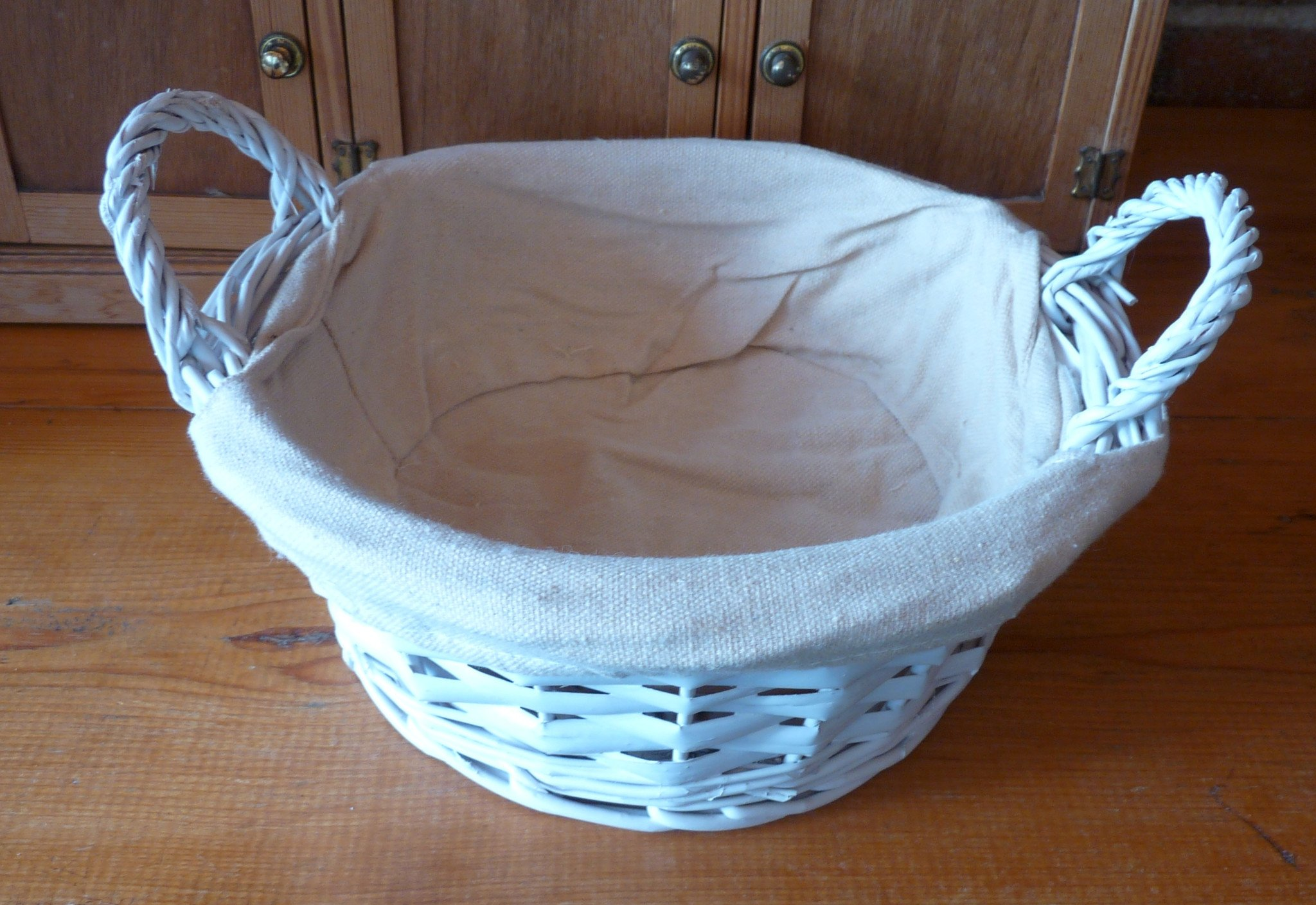 Round basket with two handles and cloth lining